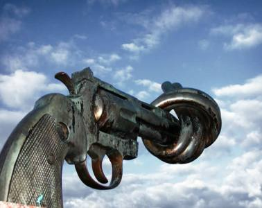This image shows a photo of Carl Fredrik Reuterswärd's 'No Violence'. It is a gun with the front tied in a knot.
