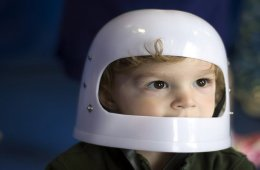 The image shows a young child with a plastic astronaut helmet on his head.
