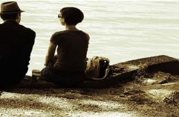 This image shows a couple sitting by the water's edge.