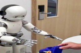 Images shows a childlike robot reaching for a hat.