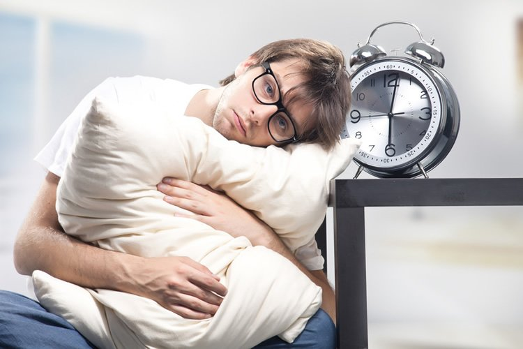 This image shows a tired looking man holding a pillow and sitting next to an alarm clock.