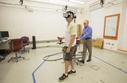 This image shows the researcher helping a student wearing the virtual reality headset.