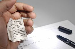 This image shows a hand holding cheat notes and an exam paper.