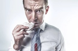 This image shows a man eating a cookie and looking guilty.