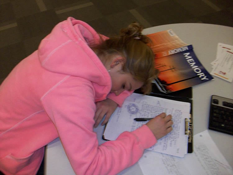 This image shows a girl sleeping next to a memory text book.
