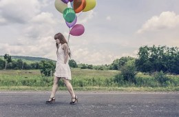 The image shows a girl walking. She is holding colorful balloons.