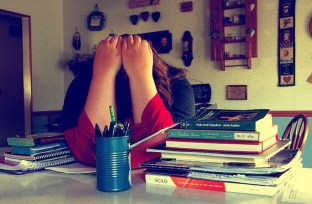 This shows a woman holding her head while resting it on a table. She is surrounded by books. The image implies the woman is stressed.