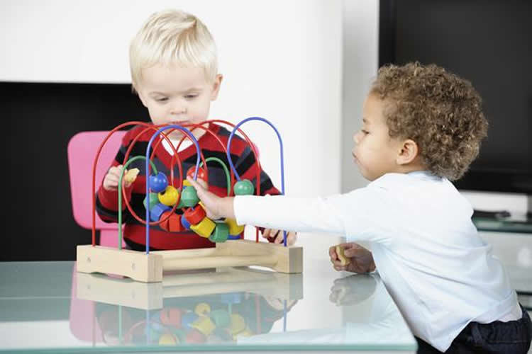 This image shows two small children playing with bricks and blocks.