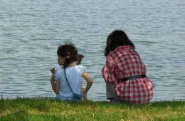 Image shows two young girls sitting next to a lake.