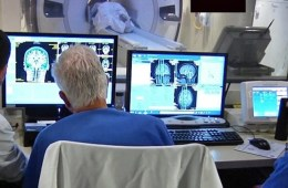 Image shows researchers looking at brain scans.