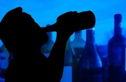 Shadowy image of a man drinking from a bottle.