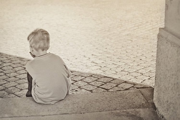 Image shows small child sitting on some steps.