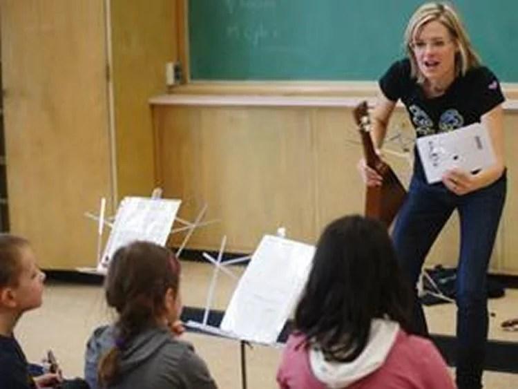 Image shows a music teacher giving a class.