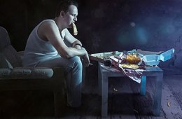 Photo of a man eating pizza in the dark.