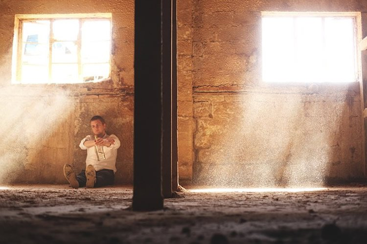 Image shows a man looking lonely, sitting by a wall.