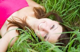 Image shows a woman smilling, laying in the grass.