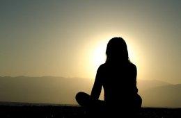 Image shows a woman meditating.
