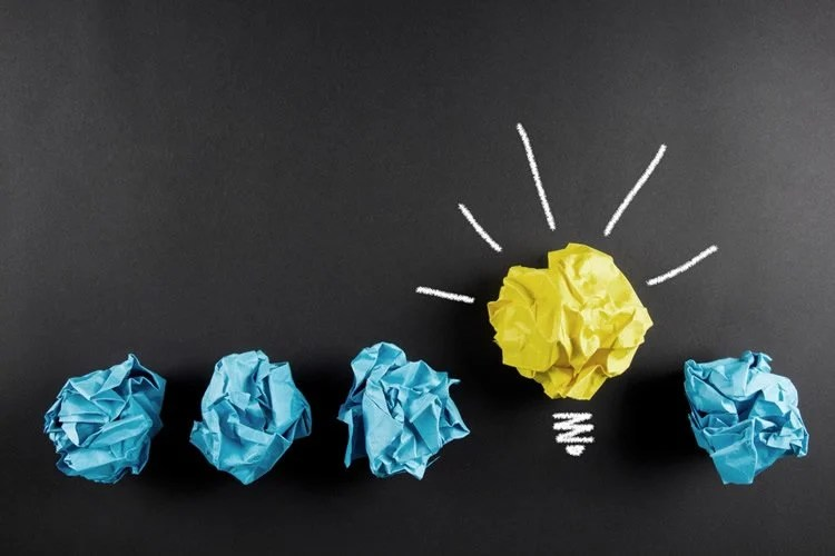 Image shows 4 pieces of blue scrunched up paper and one piece of yellow paper drawn into a lightbulb shape.