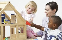 Image shows two children playing with a doll house.