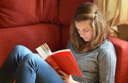 Image shows a girl reading a book.
