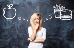 Image shows a woman thinking about an apple or burger. The food images are drawn in thought bubbles.