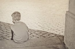Image shows a young child sitting alone.