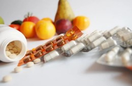 Image shows vitamin pills and fruits.