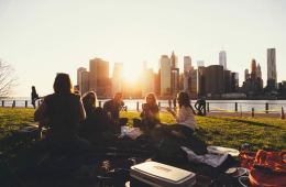 Image shows a group of people sitting in a park.