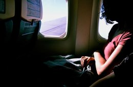 Image shows a woman on an airplane.