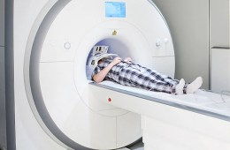 Image shows a person in an MRI scanner.