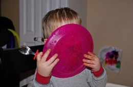 Image shows a baby licking a plate.