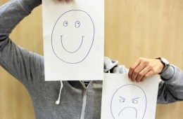Image shows a person holding up a happy face drawing and a mad face drawing.