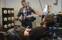 Image shows the patient using the robotic arm.