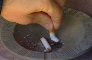 Image shows someone putting out a cigarette.