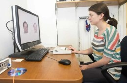 Image shows a woman looking at the faces on a computer.