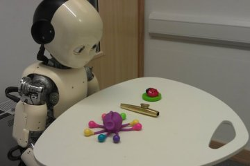 Image shows a robot toddler looking at different items on a table.