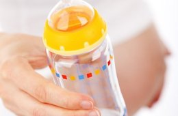 Image shows a pregnant woman holding a baby bottle.