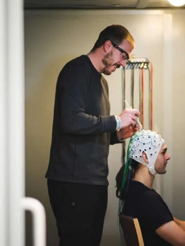 Image shows the researcher fitting an EEG cap onto a test subject.