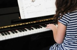 Image shows a woman playing the piano.