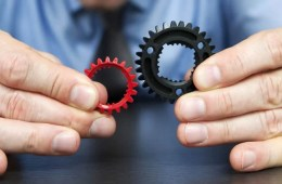 Image shows a person holding cogs.