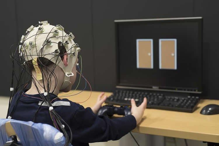 A child wearing a device that measures electrical activity in the brain chooses between doors on a computer screen. Choosing one door wins points while the other results in a loss of points. Washington University researchers have found that the brains of children with depression don't react as robustly to success in the game. Their blunted reward response is a marker of clinical depression. NeuroscienceNews image is credited to Robert Boston.