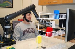 Image shows a person using the brain cap to move a robotic arm.