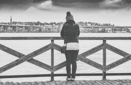 Image shows a woman on a bridge.