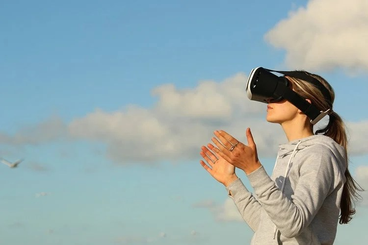 Image shows a woman wearing VR glasses.