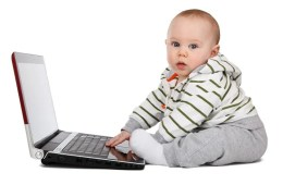 Image shows a baby playing on a laptop.