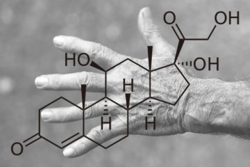 Image shows a hand and the chemical structure of cortisol.