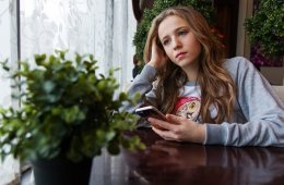 Image shows a teenaged girl playing with her phone.