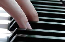 Image shows a person playing piano.