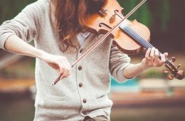 Image shows a woman playing the violin.