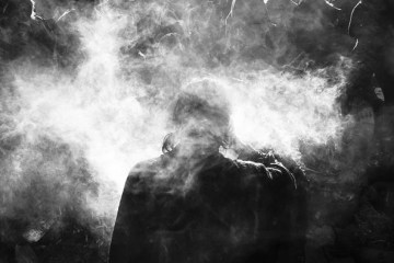 Image shows a person surrounded by smoke.